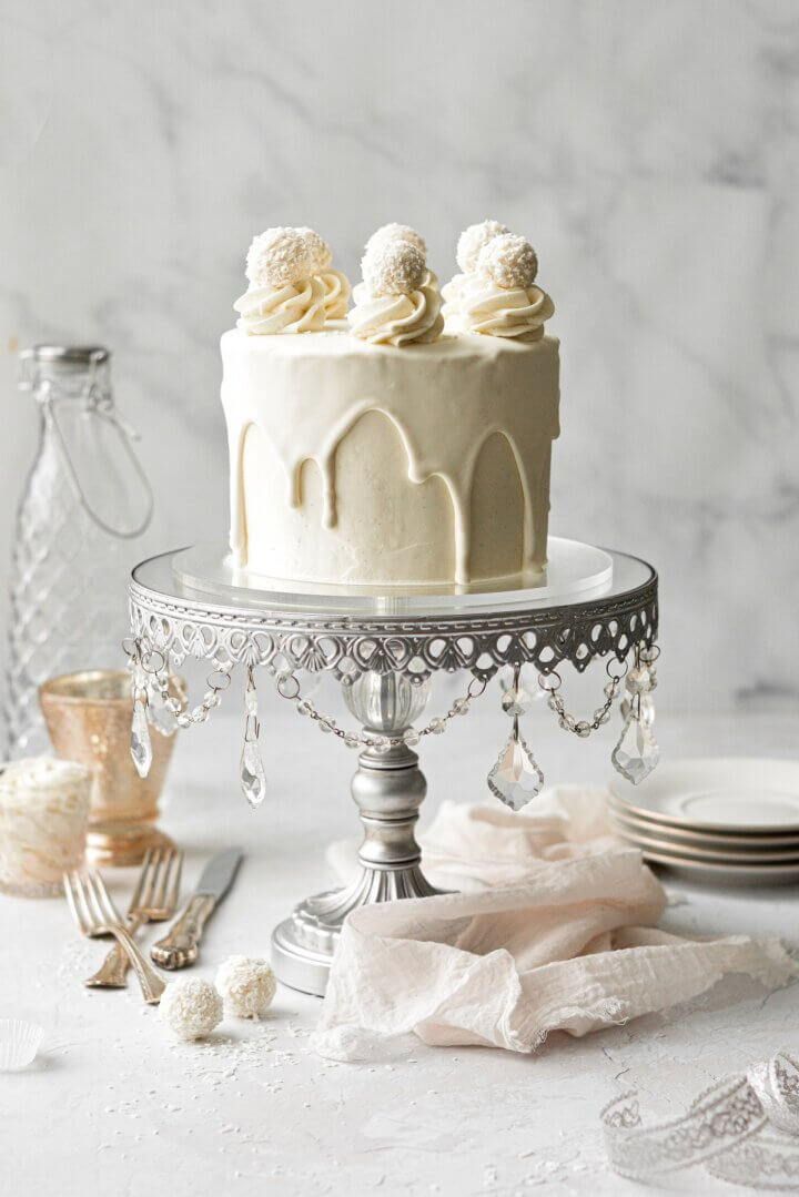 A white chocolate cake with drip and white chocolate truffles, on a silver mirrored cake stand.