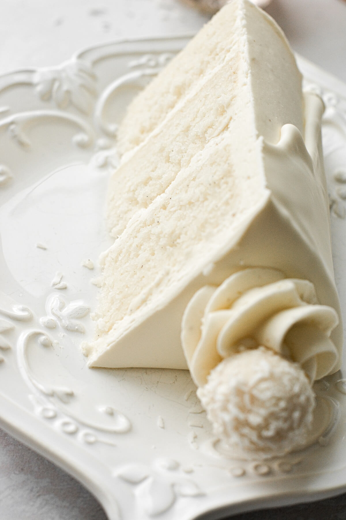 A slice of white chocolate cake topped with a white chocolate truffle.