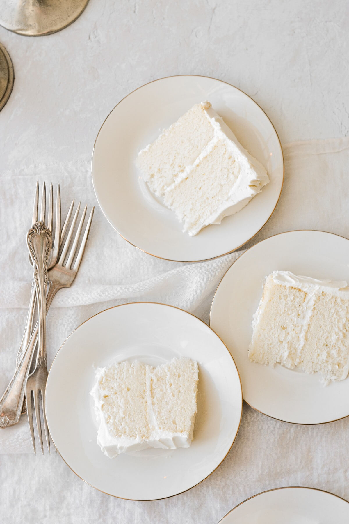 Slices of almond wedding cake on white plates.