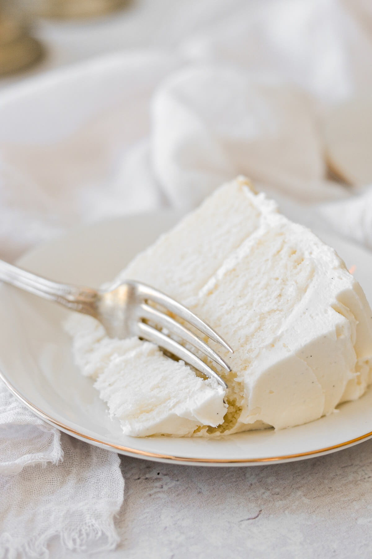 A slice of almond wedding cake with one bite taken.