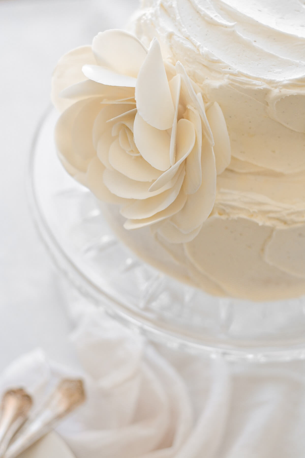 A two-tiered almond wedding cake with a white chocolate rose.