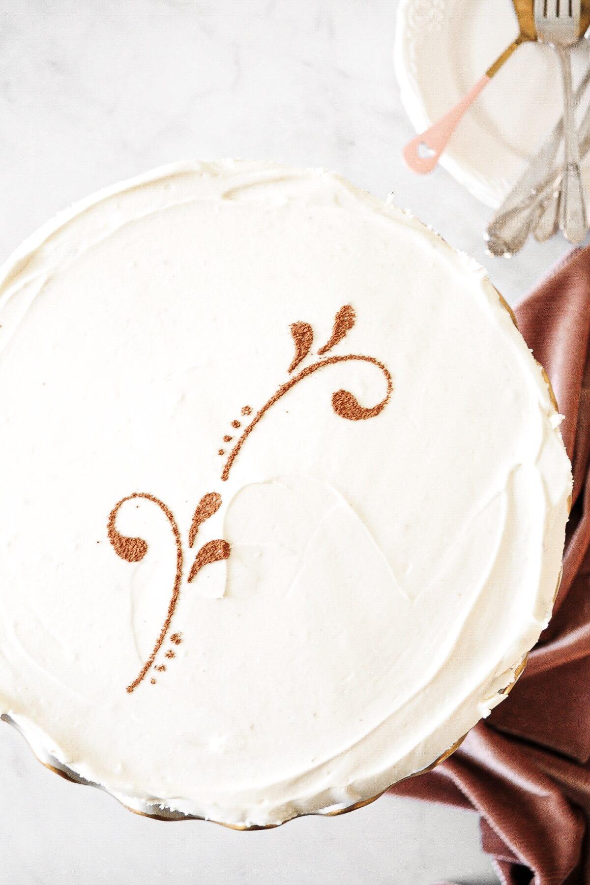 A cocoa powder stencil on top of vanilla cheesecake.