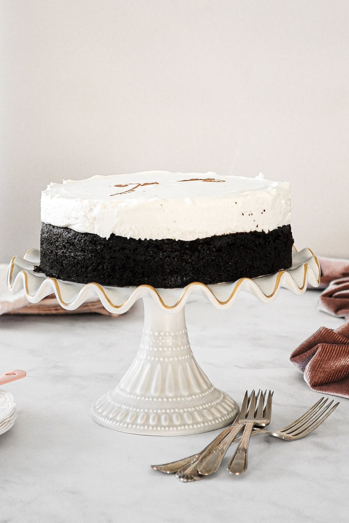 Black and white cheesecake with chocolate cake on the bottom and vanilla cheesecake on top.