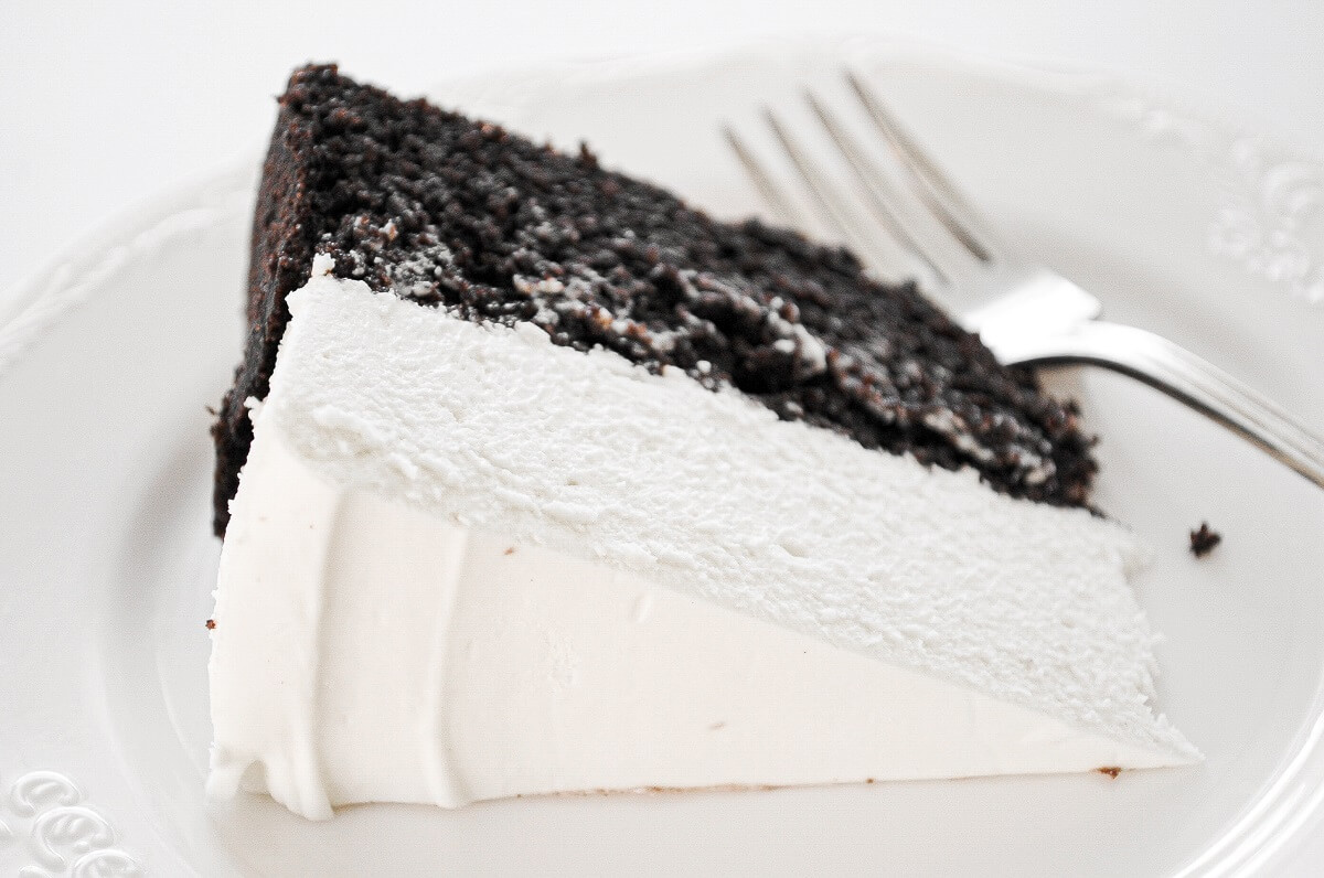 A slice of black and white cheesecake on a white plate.
