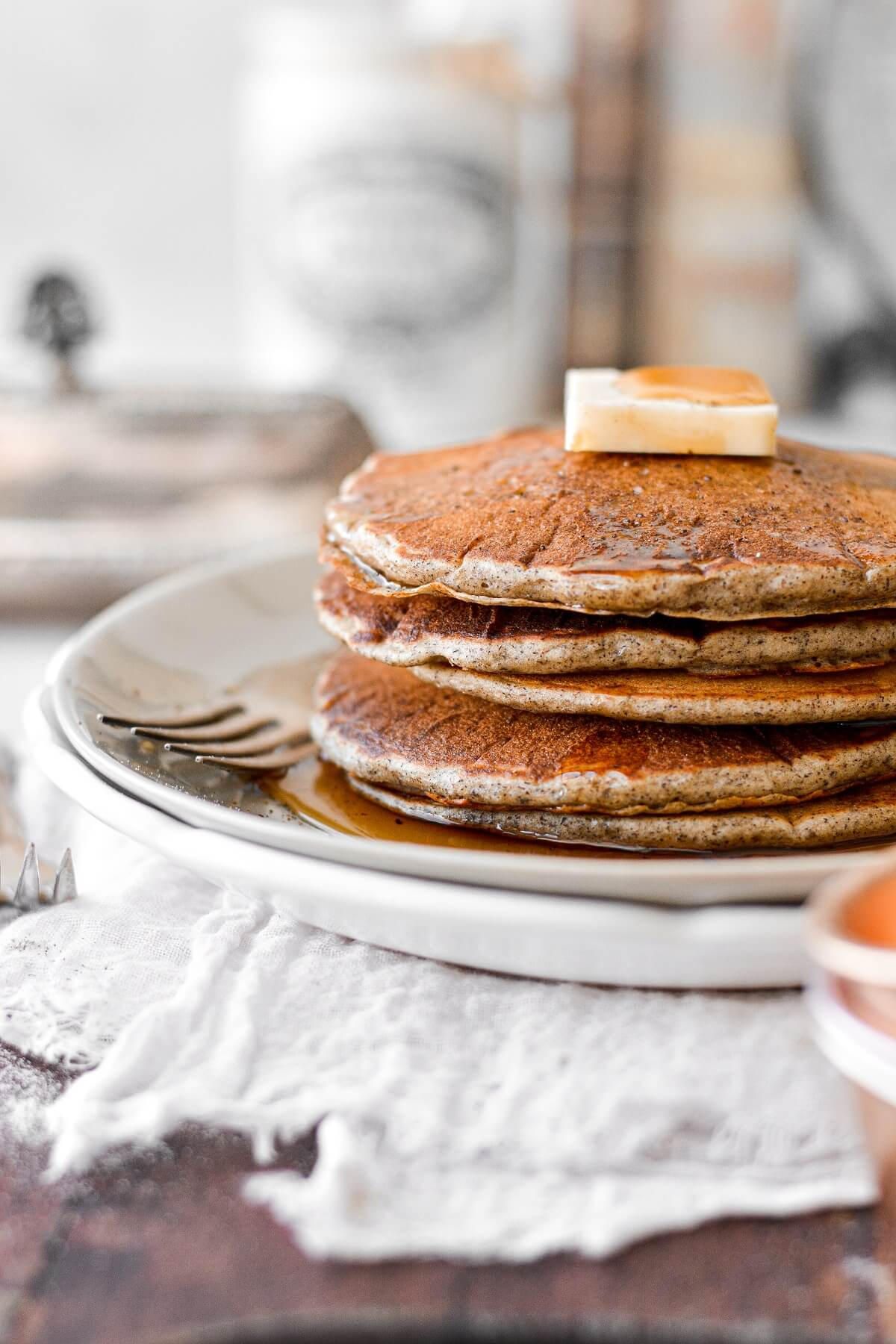 A stack of buckwheat pancakes with maple syrup and butter.