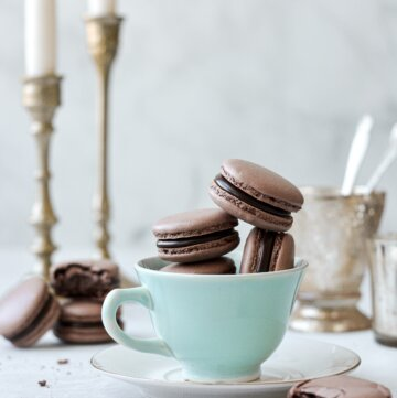 Chocolate macarons, filled with dark chocolate ganache, arranged in a vintage tea cup.