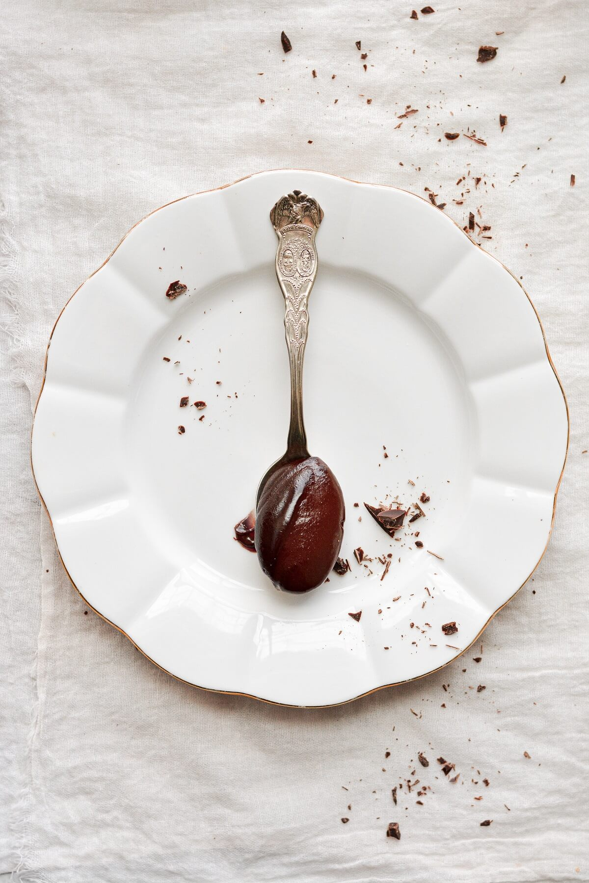 A spoonful of chocolate pudding resting on a white plate.