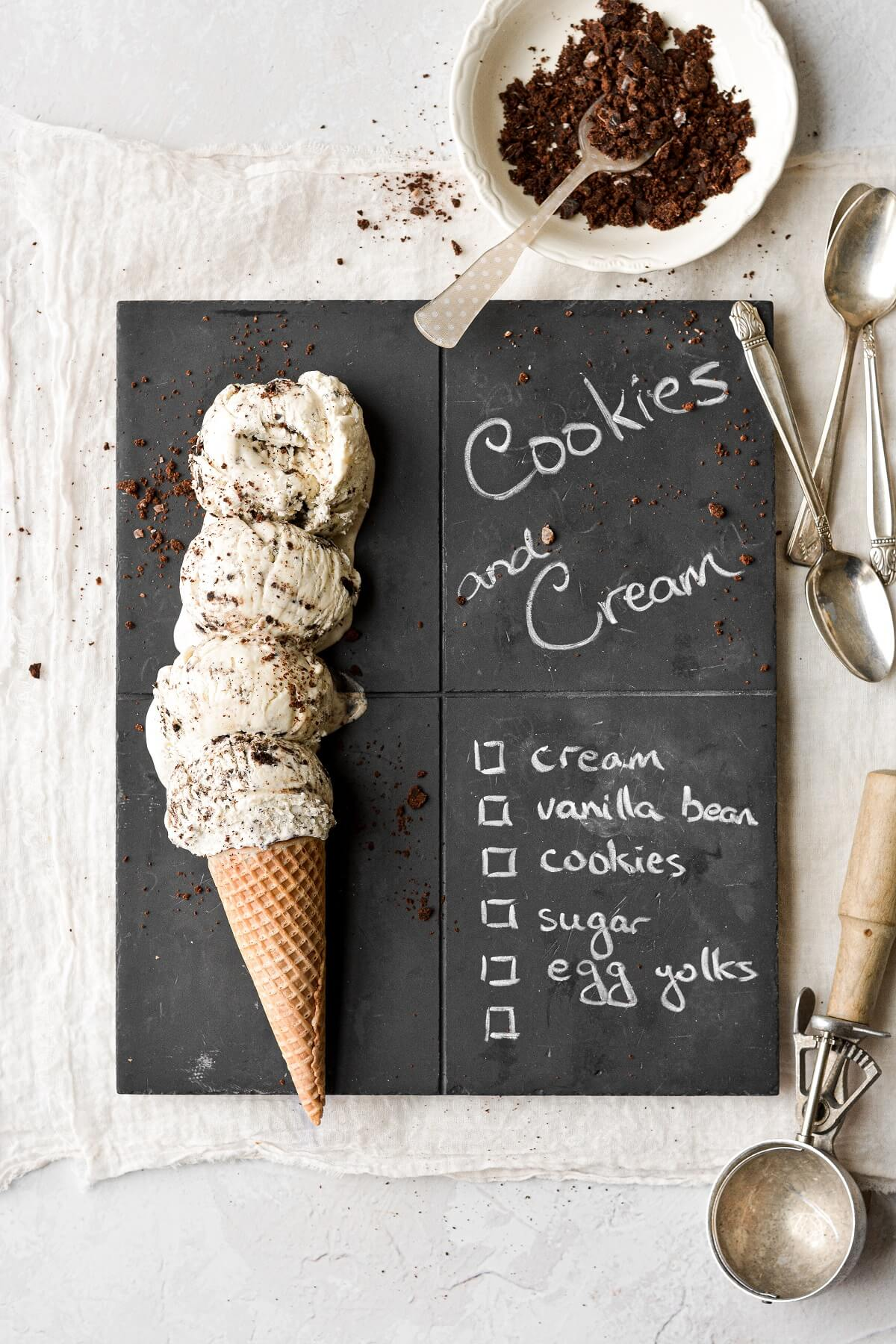Scoops of cookies and cream ice cream on a chalkboard serving board.