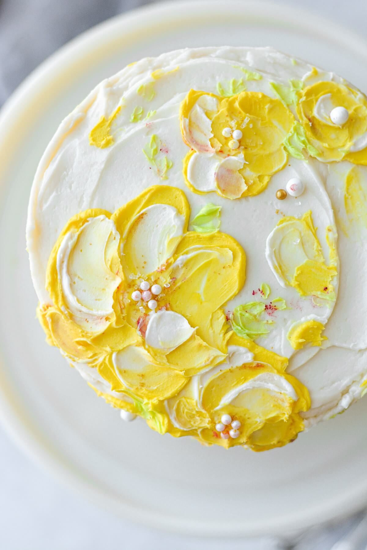 Hummingbird cake with yellow painted floral buttercream.