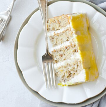 A slice of hummingbird cake on a white plate.