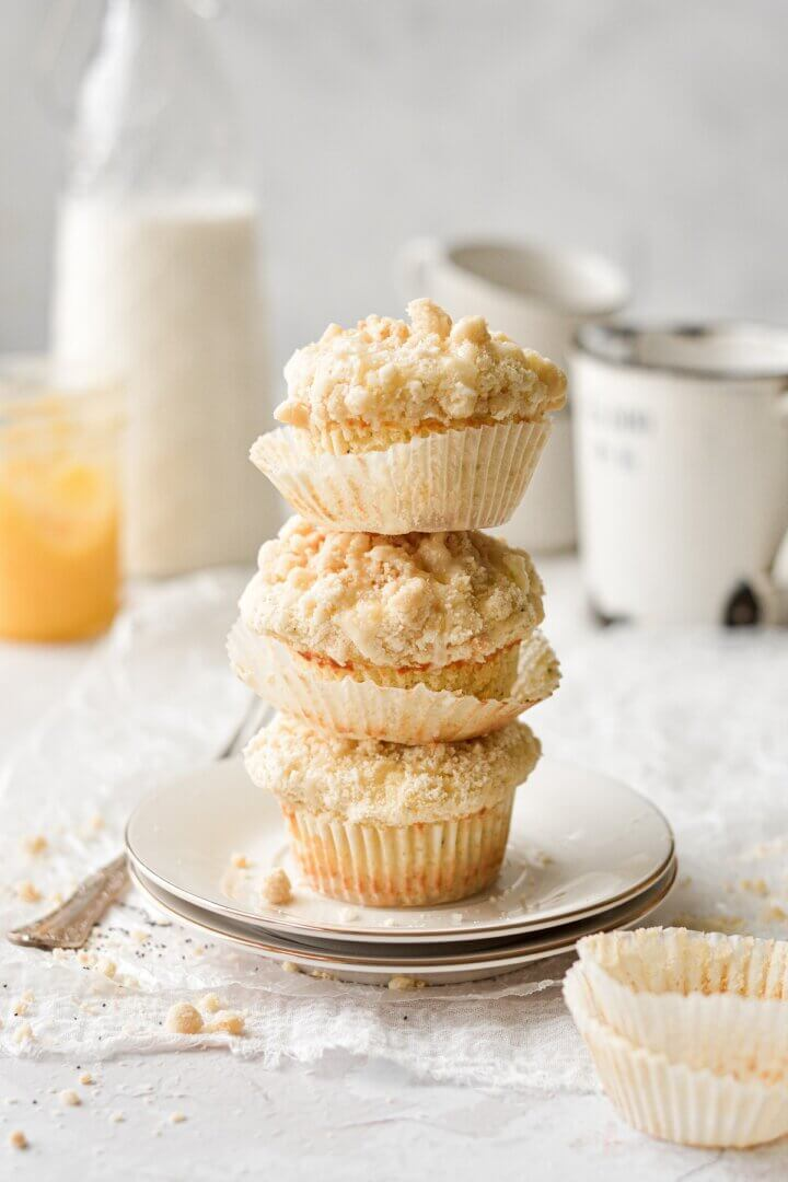 A stack of three lemon poppy seed crumb muffins on a plate.