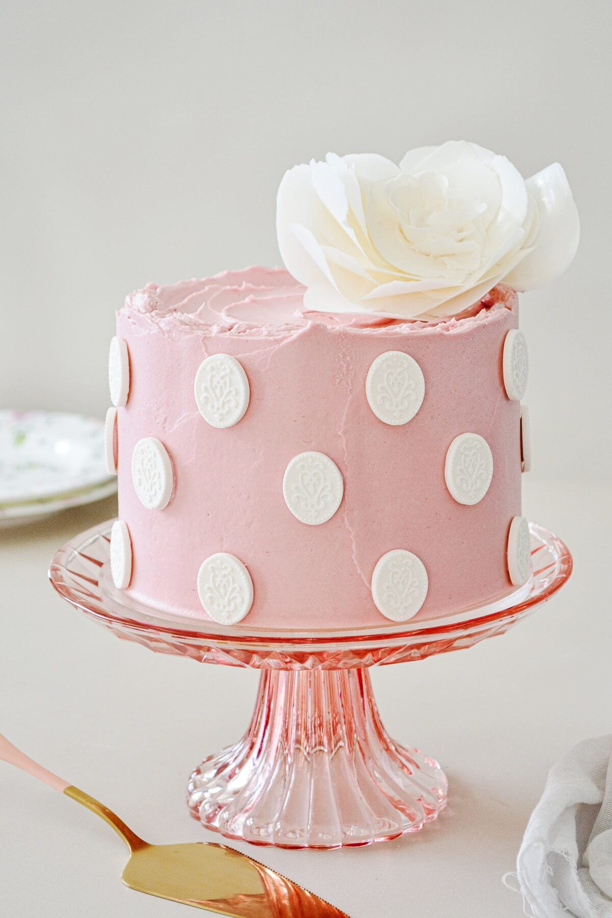 Lemon raspberry cake on a pink cake pedestal, topped with a white chocolate flower.