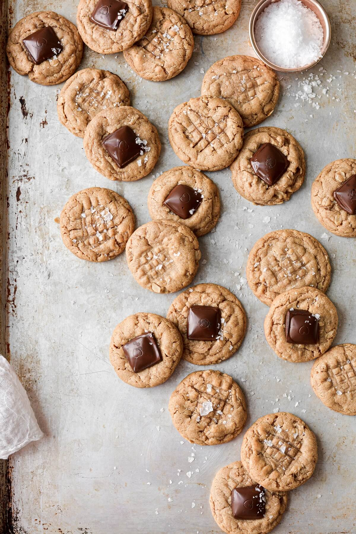 Peanut butter cookies, some topped with squares of chocolate, sprinkled with flaky salt.