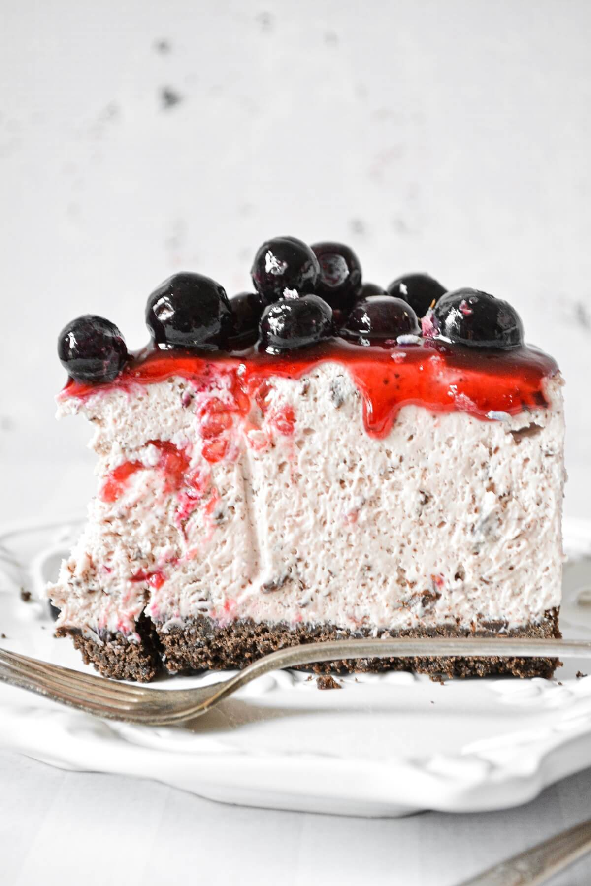 Raspberry blueberry cheesecake, with a chocolate crust, topped with fruit compote.