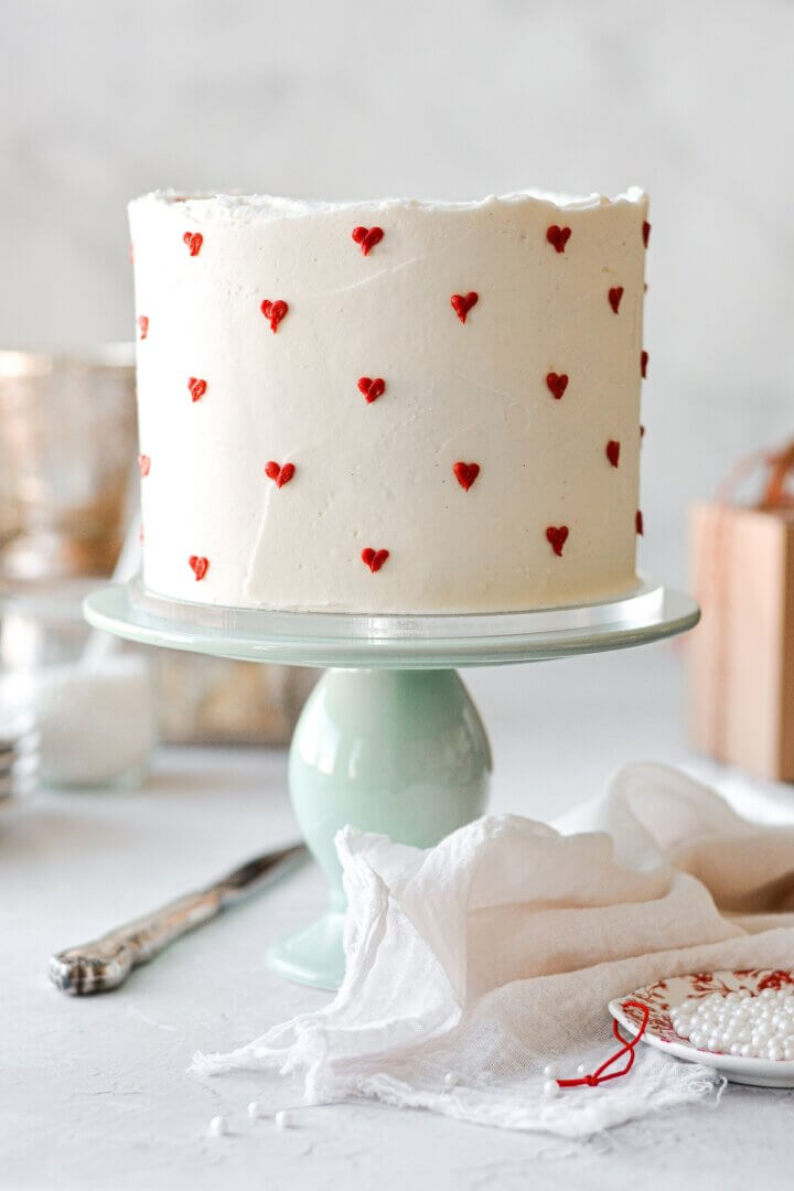 A Valentine's cake with red hearts piped onto white buttercream.