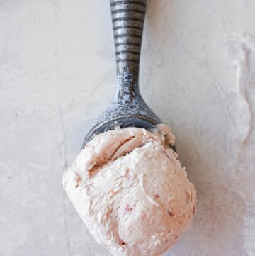 A scoop of roasted rhubarb ice cream in a vintage ice cream scoop.