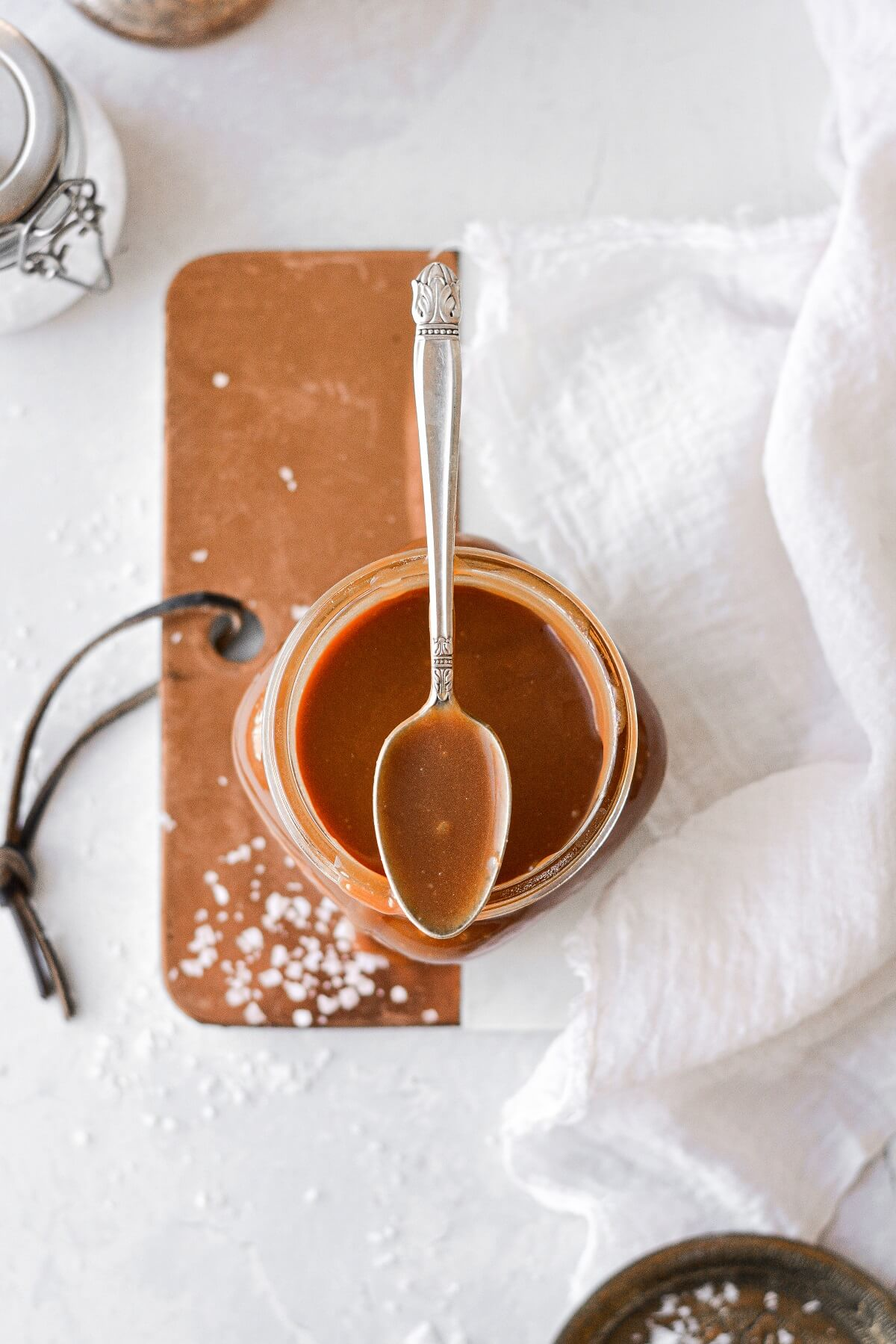 A jar of salted caramel sauce with a spoon resting on top.