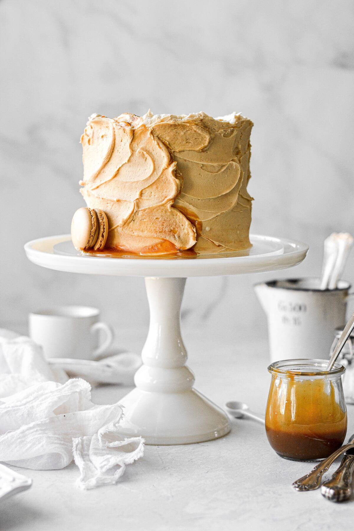 Caramel cake on a white cake pedestal.