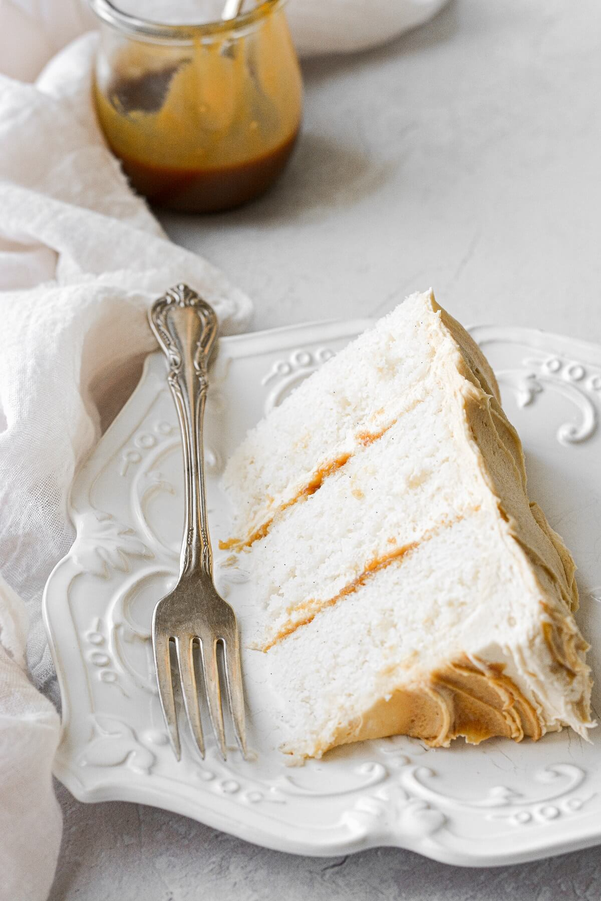 A slice of vanilla cake with salted caramel buttercream.
