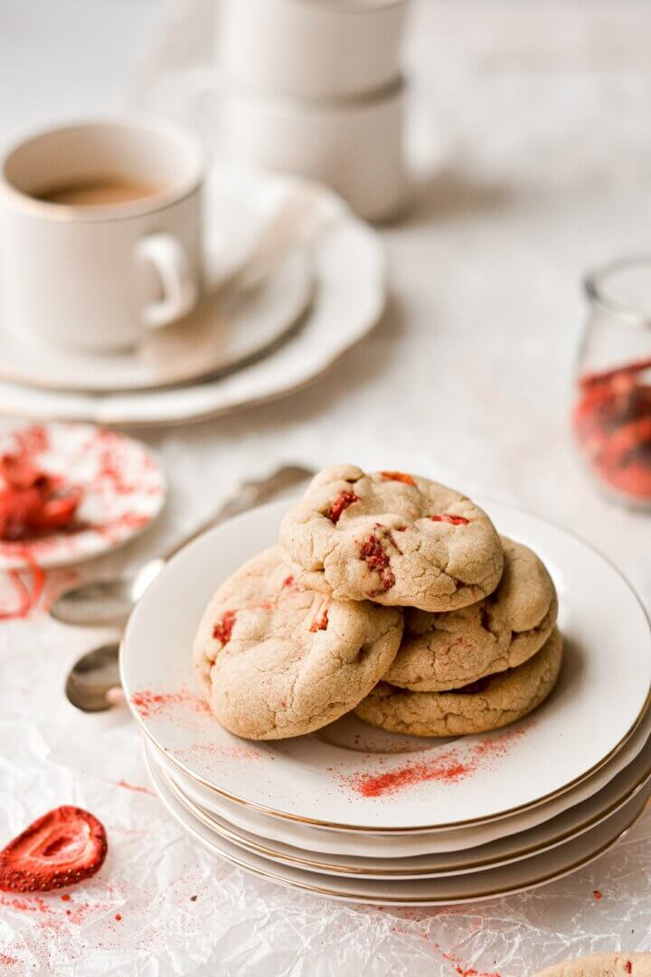 Strawberry brown butter cookies on a stack of plates.