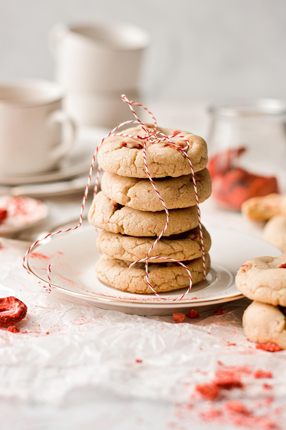 A stack of strawberry brown butter cookies tied with red and white twine.