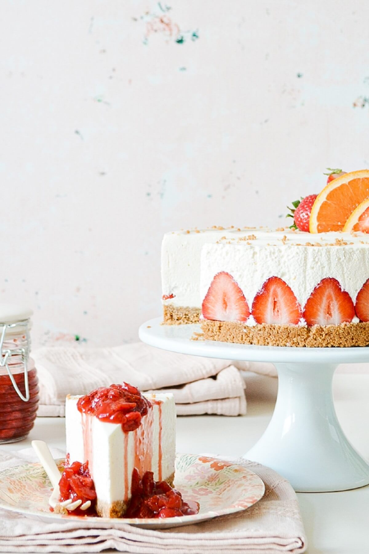 Strawberry orange cheesecake with a slice topped with strawberry sauce.