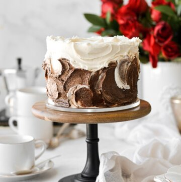Vanilla latte cake with swirls of vanilla and chocolate espresso buttercream, next to a vase of red roses.