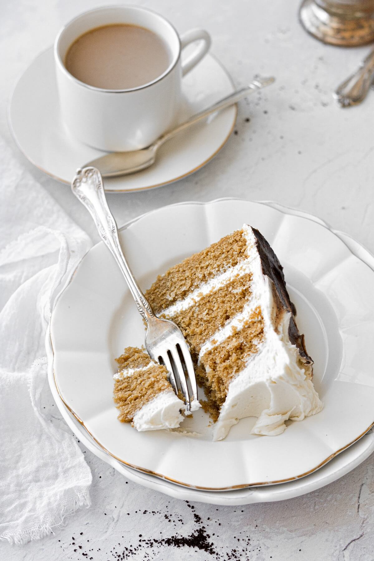 A slice of vanilla latte cake with a bite cut, next to a cup of coffee.