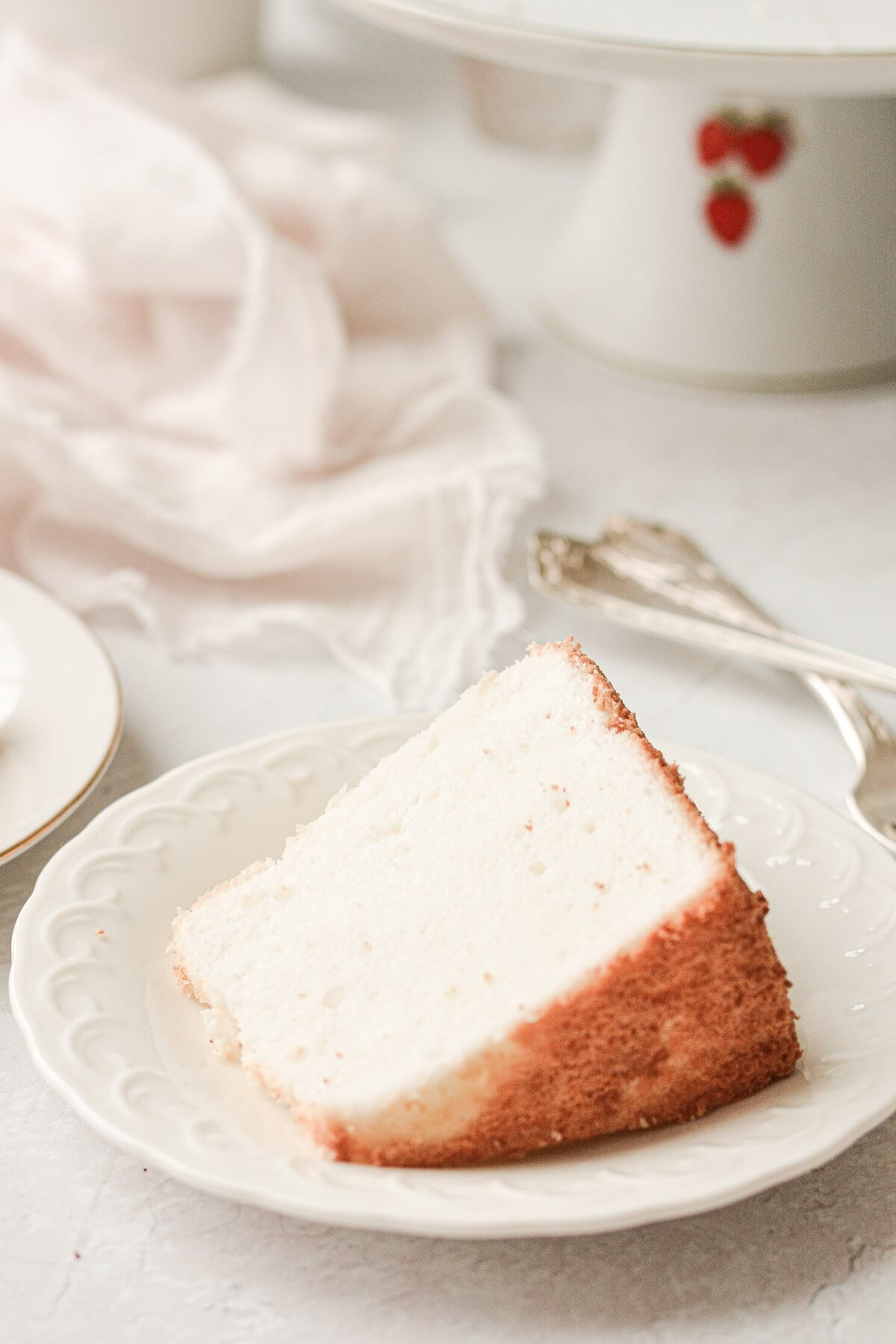 A slice of angel food cake on a white plate.