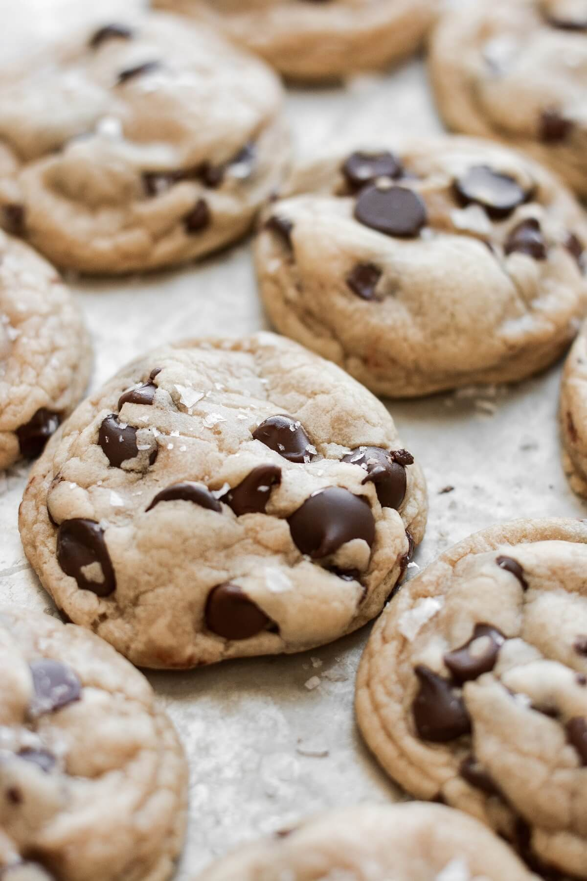 High altitude chocolate chip cookies, arranged on a baking sheet and sprinkled with sea salt.