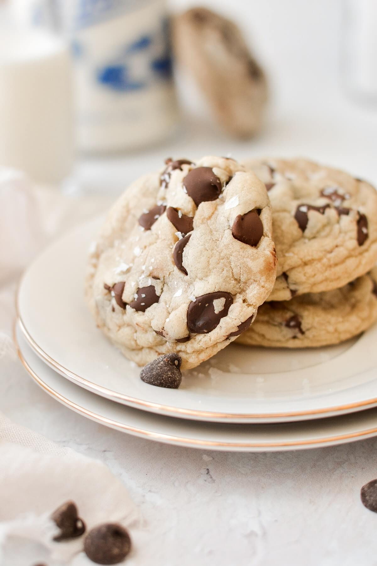 High altitude chocolate chip cookies, on a plate, with jars of milk.