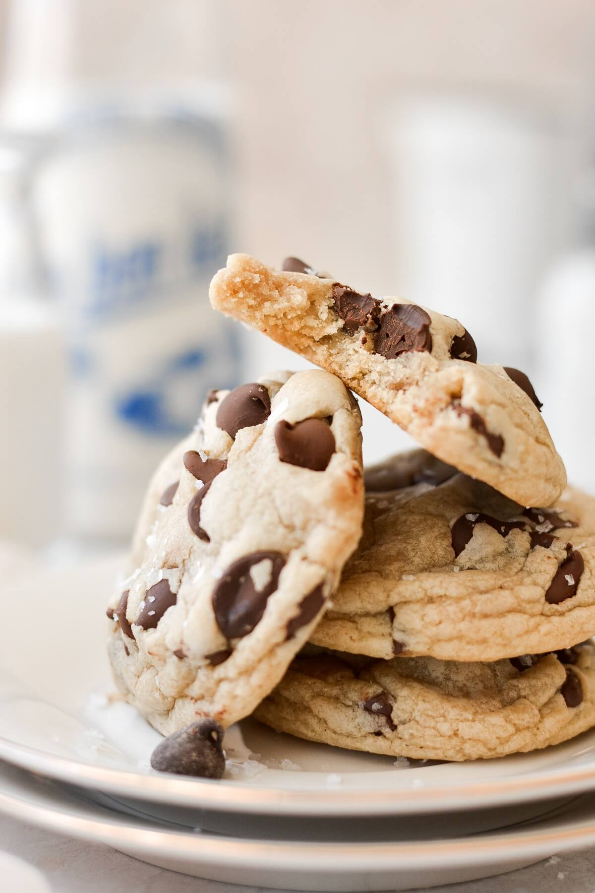 A stack of chocolate chip cookies, one with a bite taken out.