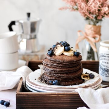 Chocolate pancakes topped with bananas, blueberries and chopped chocolate.