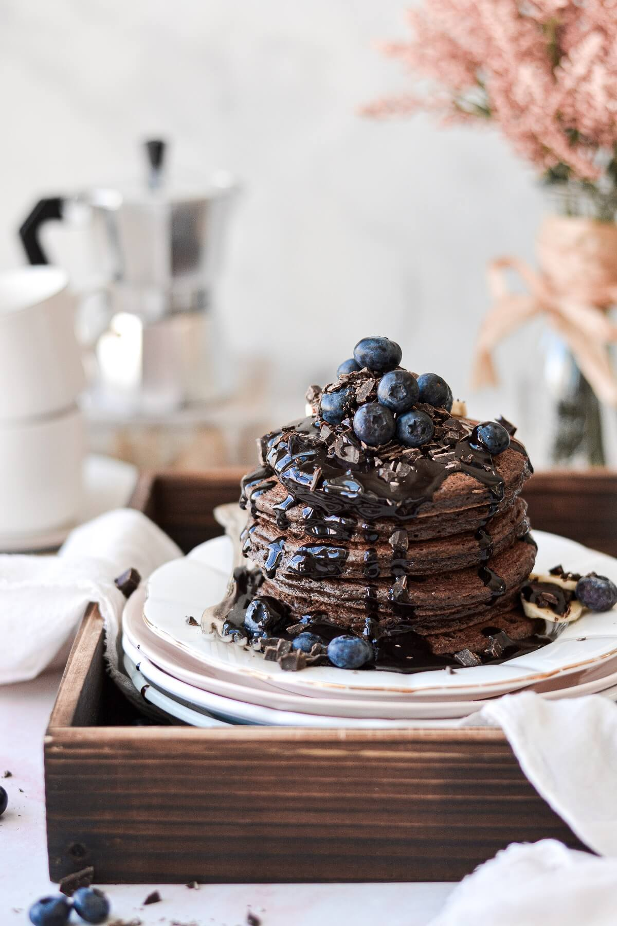 Chocolate pancakes topped with chocolate syrup, chopped chocolate and blueberries.