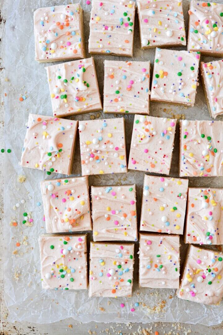 Soft frosted sugar cookie bars, cut into squares, with pale pink frosting and sprinkles.