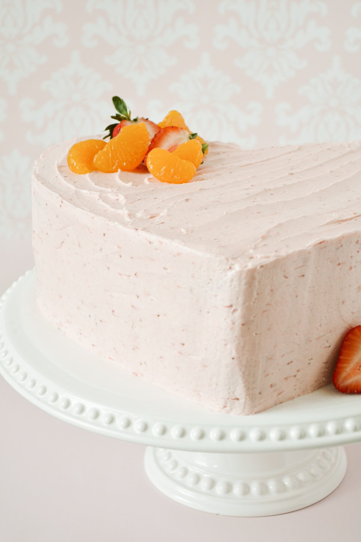 Heart shaped strawberry orange cake, topped with sliced strawberries and mandarin oranges.