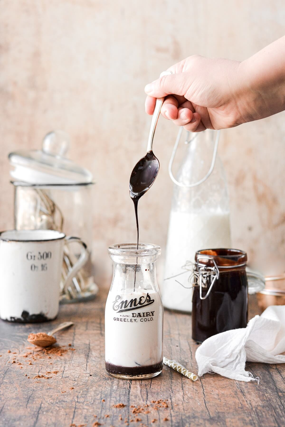 A spoonful of homemade chocolate syrup, drizzled into a vintage milk jar.