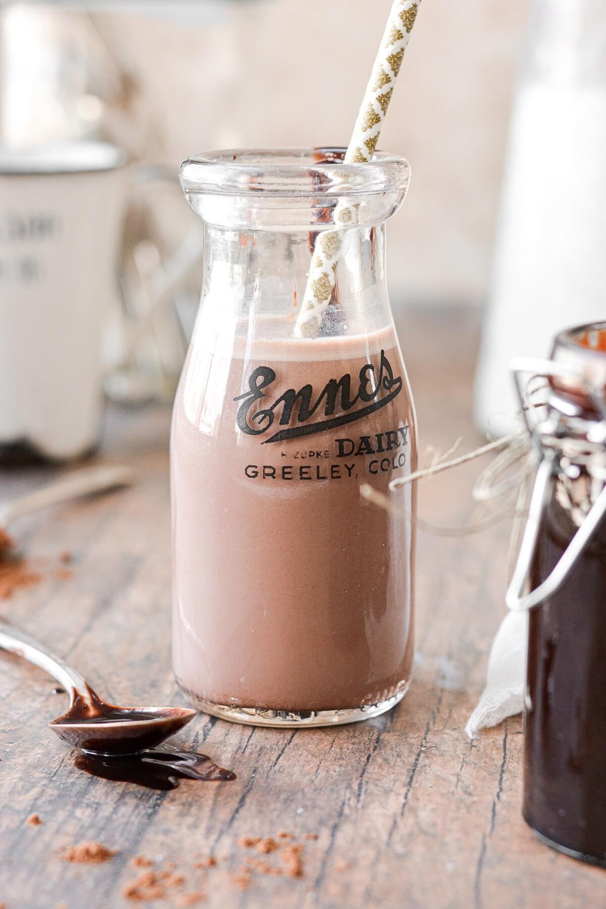 A vintage milk jar filled with chocolate milk, made from homemade chocolate syrup..