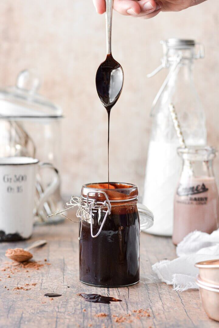 A spoonful of homemade chocolate syrup, drizzling into a jar of syrup..