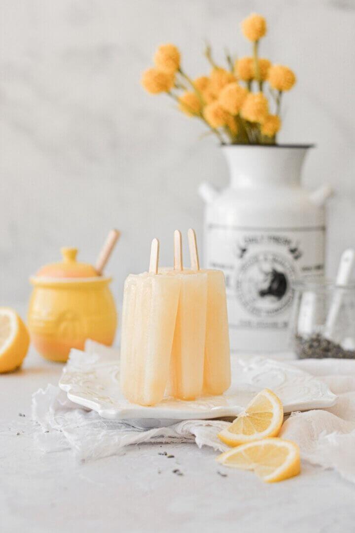 Lavender lemonade honey popsicles, propped against each other on a white plate.