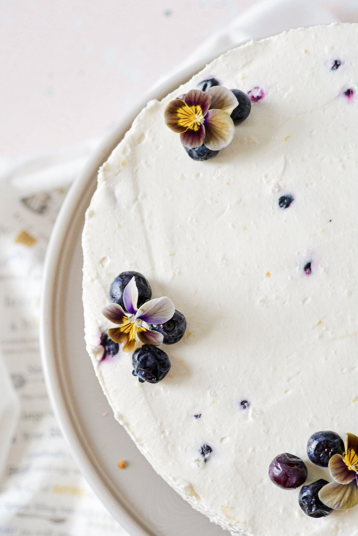 Lemon blueberry cheesecake, decorated with blueberries and edible flowers.