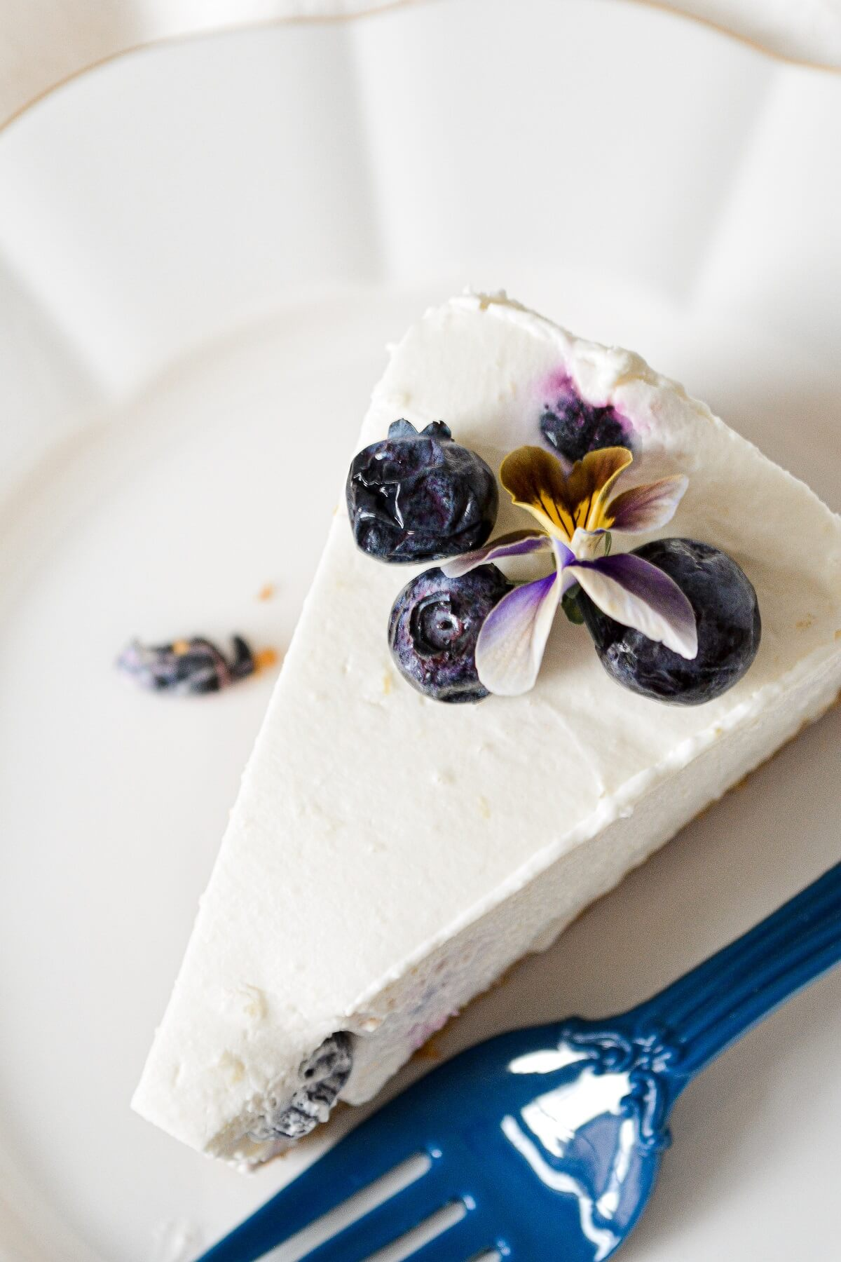 A slice of lemon blueberry cheesecake, decorated with blueberries and edible flowers.
