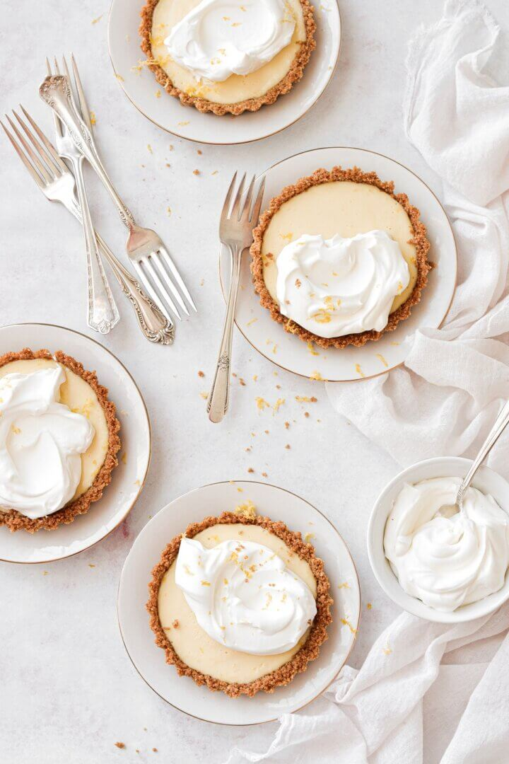 Lemon icebox pie, baked in individual lemon tarts, topped with whipped cream.