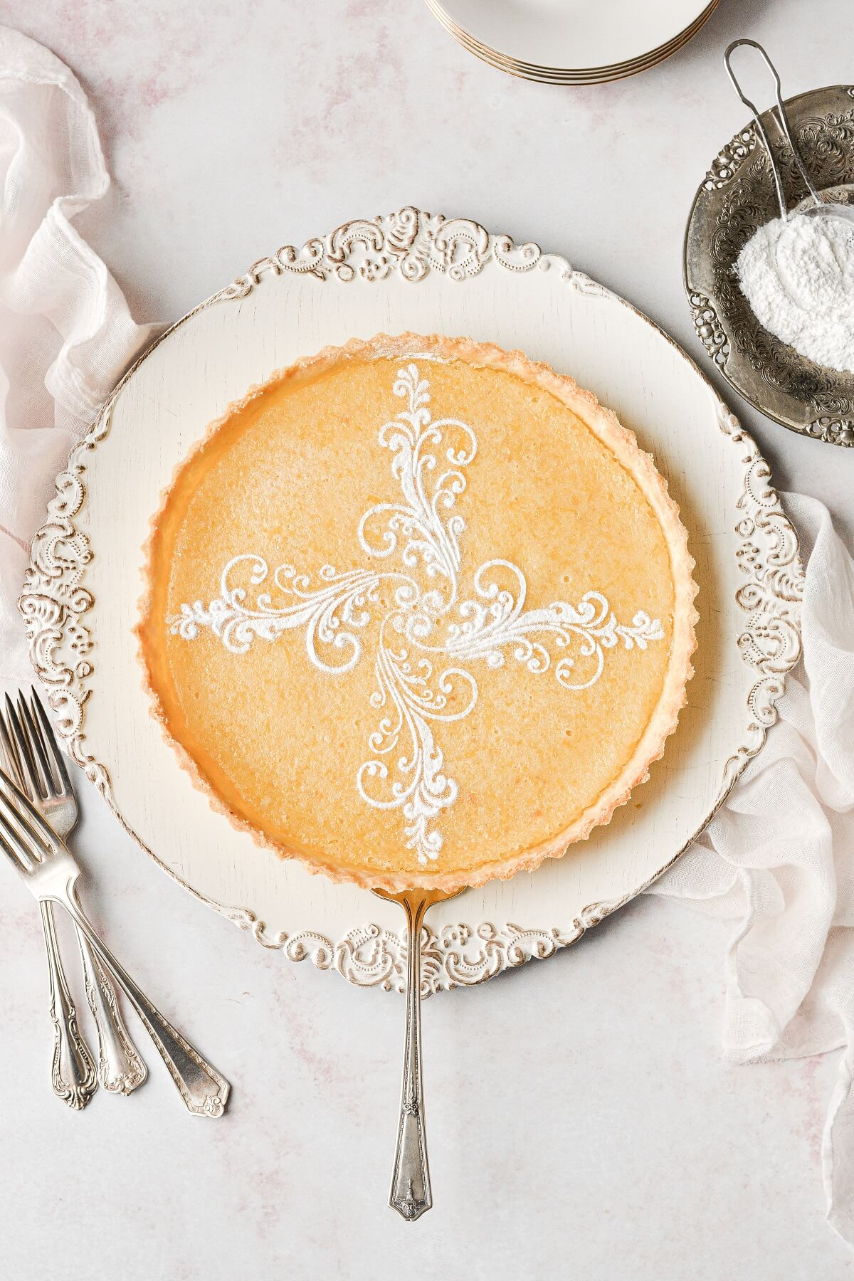 A lemon tart with a fancy powdered sugar stencil.