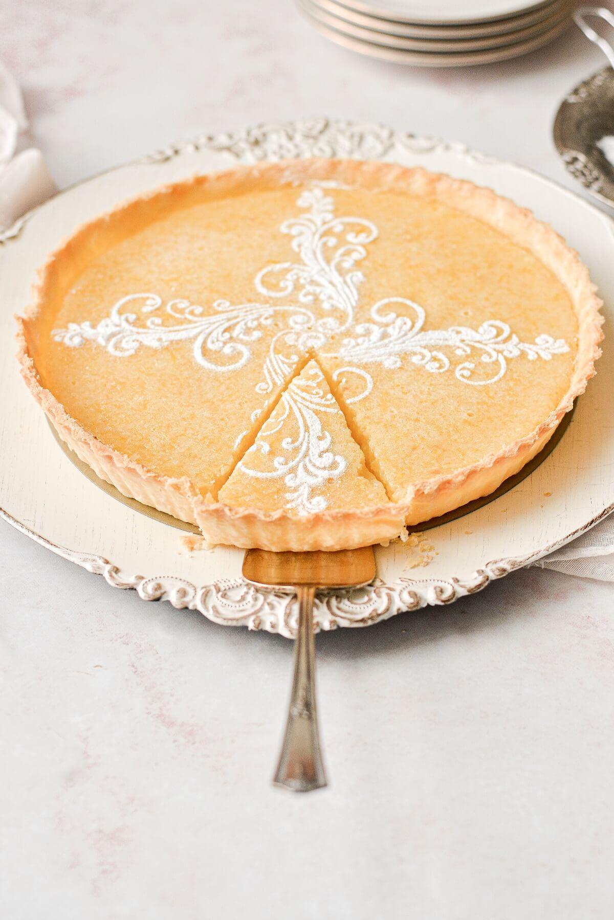 A lemon tart with one slice cut.