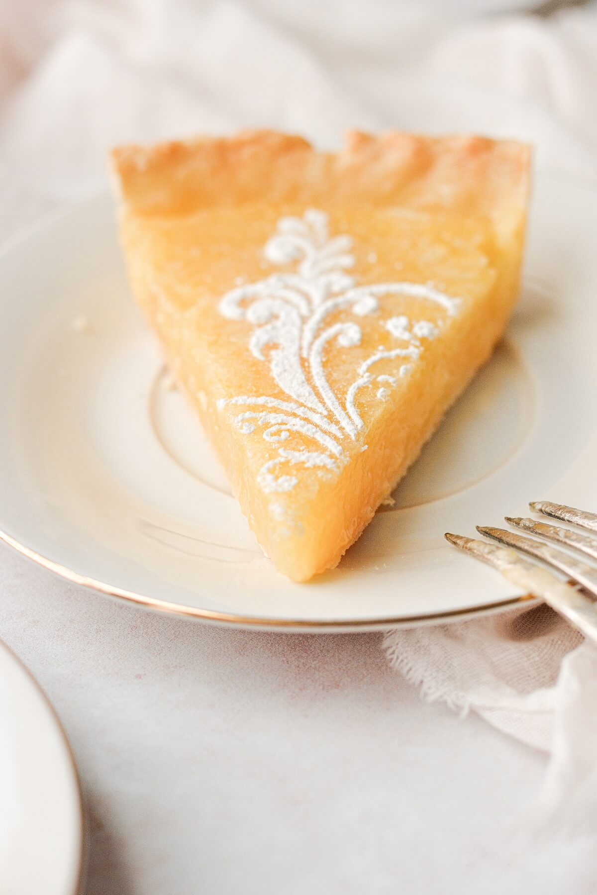 A slice of lemon tart with a powdered sugar stencil on top.