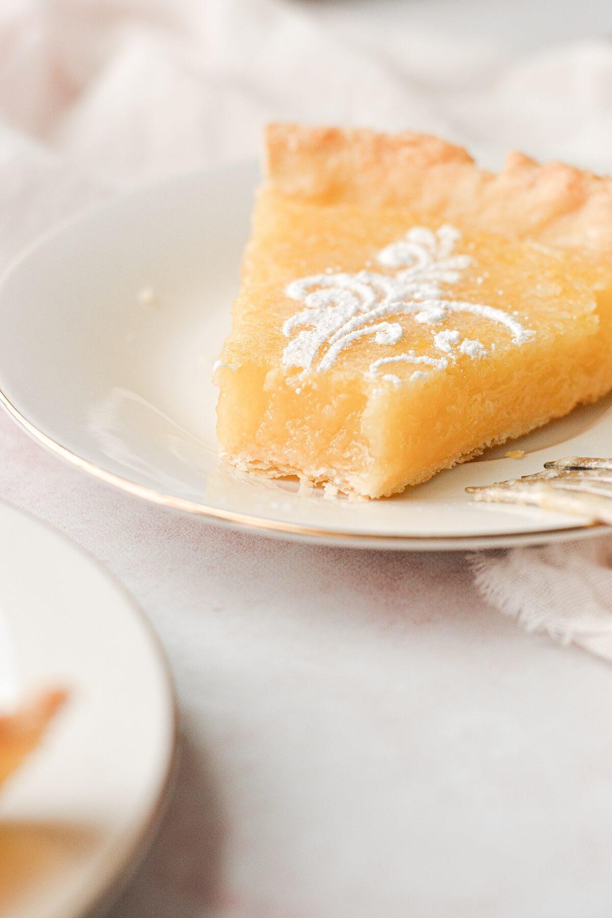 A slice of lemon tart with a bite taken.