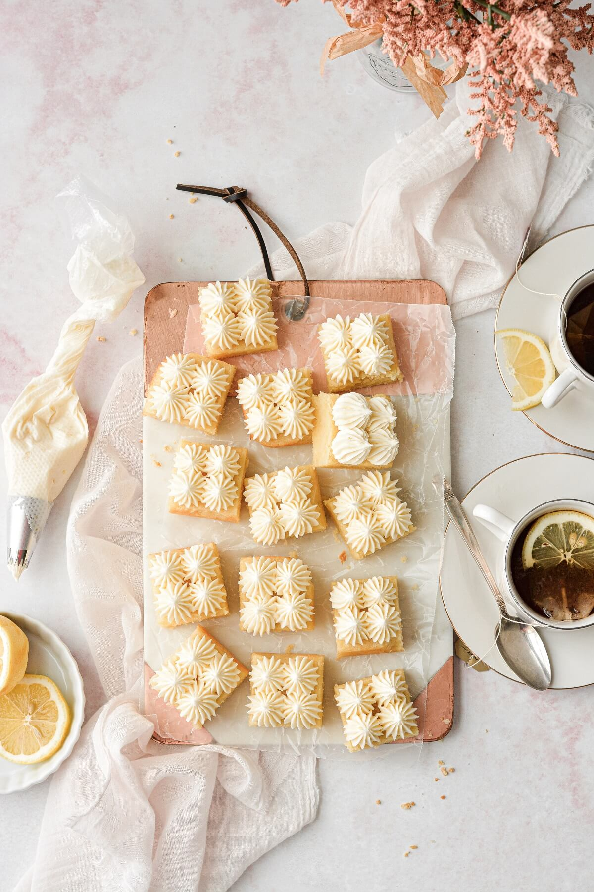 Lemonies, or lemon brownies, cut into squares and frosted with piped lemon buttercream.