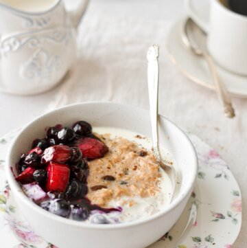 A bowl of oatmeal topped with blueberry rhubarb compote, with cups of coffee.