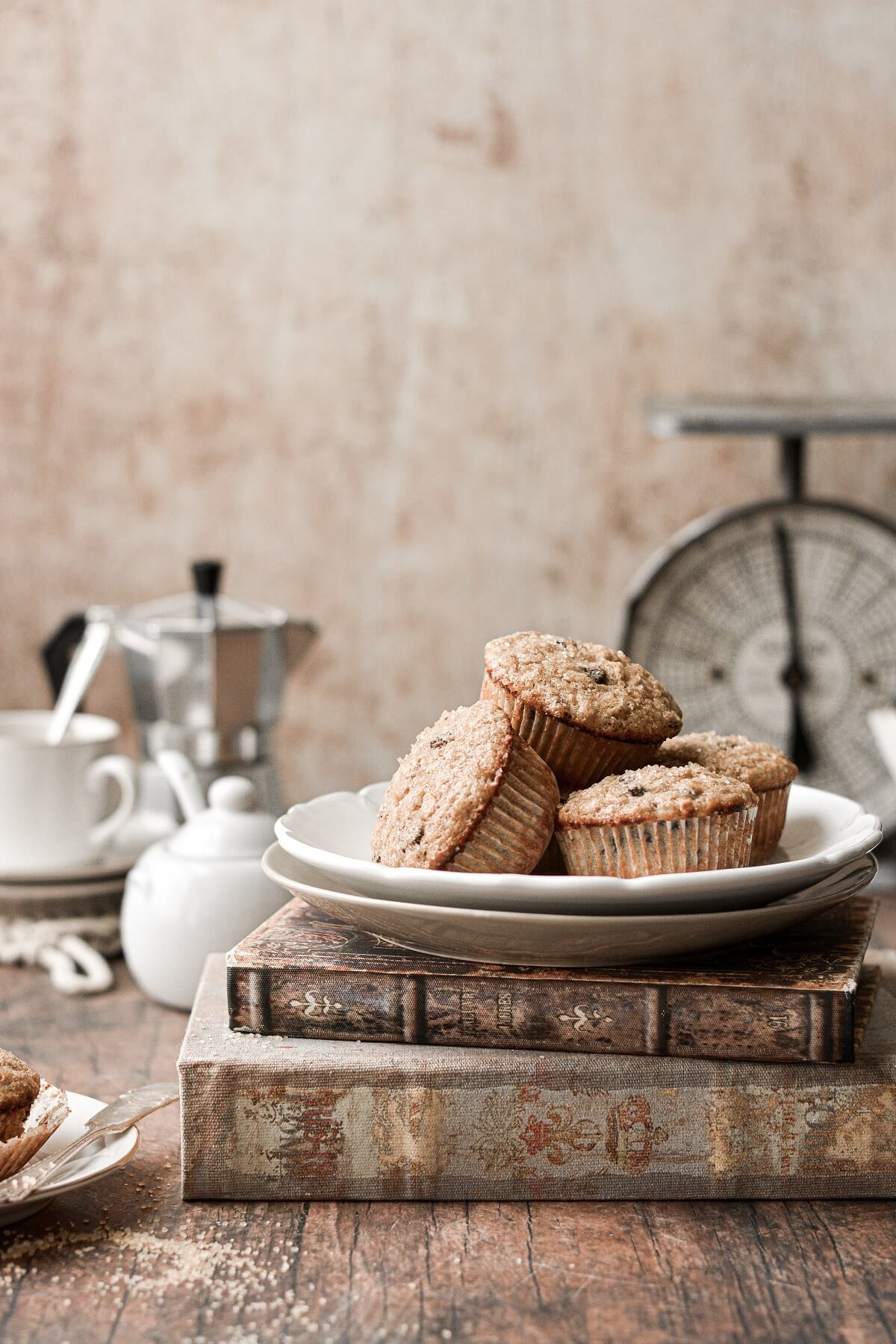 Oatmeal raisin muffins, piled on a plate, next to a cup of coffee.